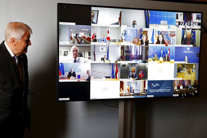 Federal Minister of the Interior Horst Seehofer poses for a group photo at a virtual meeting with the European justice and interior ministers in the context of the German EU Council presidency due to the Corona crisis in Berlin, Germany, Tuesday, July 7, 2020. (Fabrizio Bensch/Pool via AP)