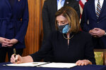 House Speaker Nancy Pelosi of Calif., signs the article of impeachment against President Donald Trump in an engrossment ceremony before transmission to the Senate for trial on Capitol Hill, in Washington, Wednesday, Jan. 13, 2021. (AP Photo/Alex Brandon)