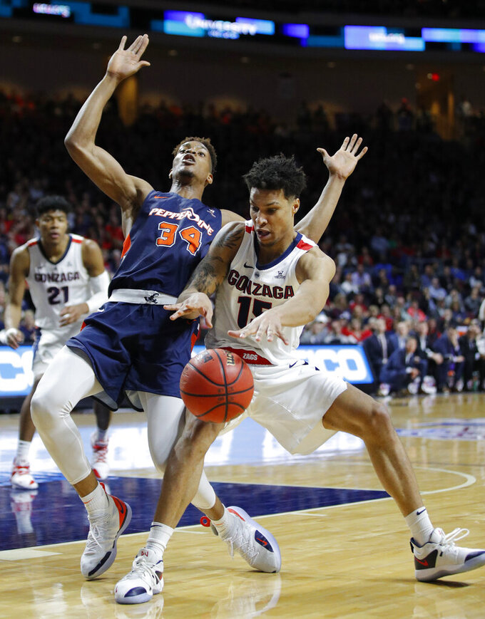 Gonzaga's Brandon Clarke drives around Pepperdine's Victor Ohia Obioha during the first half of an NCAA semifinal college basketball game at the West Coast Conference tournament, Monday, March 11, 2019, in Las Vegas. (AP Photo/John Locher)