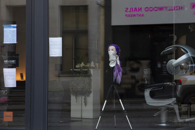 A mannequin head with a scarf around the nose and mouth is placed on a tripod in the window of a hairdressing salon in Antwerp, Belgium, Monday, March 23, 2020. After Belgian Prime Minister Sophie Wilmes announced that hairdressers would still be able to operate, while many other stores were required to be closed during the coronavirus epidemic, some thought it was a bad Belgian joke. Fearing for their health, some hairdressers now are calling on the government to order the closure of all salons without delay. For most people, the new coronavirus causes only mild or moderate symptoms, such as fever and cough. For some, especially older adults and people with existing health problems, it can cause more severe illness, including pneumonia. (AP Photo/Virginia Mayo)