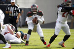 Tampa Bay Buccaneers quarterback Jameis Winston, center, scrambles from the pocket during the first half of an NFL football game against the Jacksonville Jaguars, Sunday, Dec. 1, 2019, in Jacksonville, Fla. (AP Photo/Stephen B. Morton)