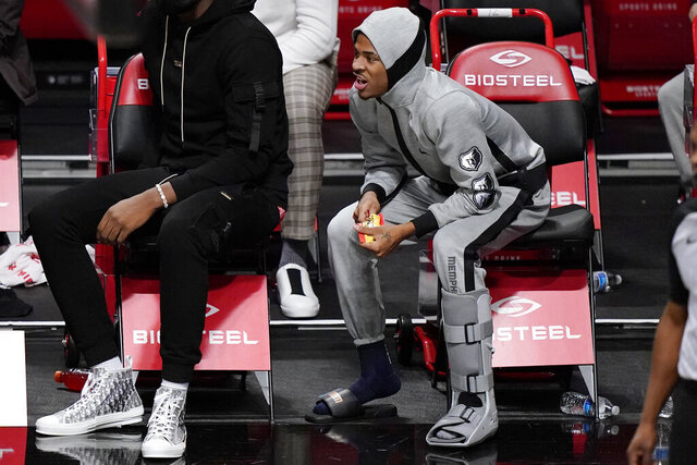Memphis Grizzlies guard Ja Morant, right, wears a boot on his left foot after suffering an injury during the team's NBA basketball game against the Brooklyn Nets, Monday, Dec. 28, 2020, in New York. (AP Photo/Kathy Willens)
