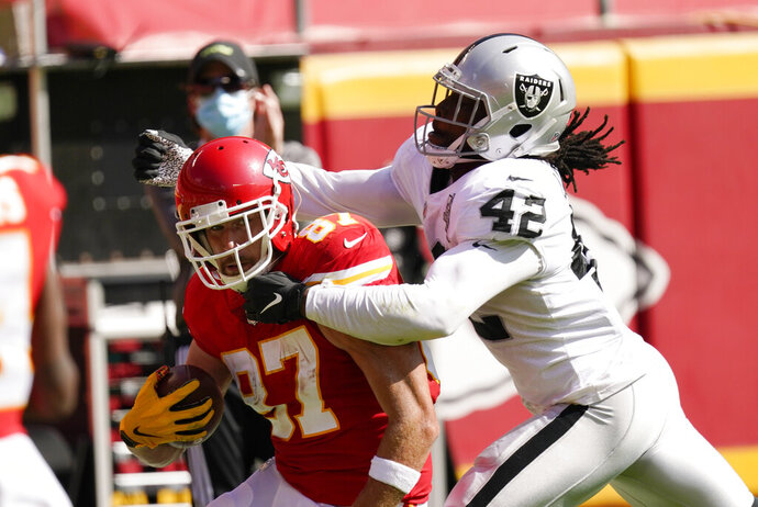 Kansas City Chiefs tight end Travis Kelce (87) tries to break a tackle by Las Vegas Raiders linebacker Cory Littleton (42) during the first half of an NFL football game, Sunday, Oct. 11, 2020, in Kansas City. (AP Photo/Charlie Riedel)