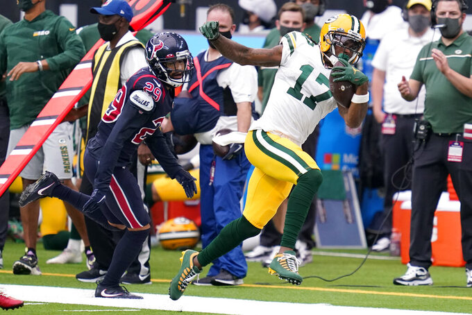 Green Bay Packers wide receiver Davante Adams (17) tries to stay in bounds as Houston Texans cornerback Phillip Gaines (29) watches during the first half of an NFL football game Sunday, Oct. 25, 2020, in Houston. (AP Photo/Sam Craft)