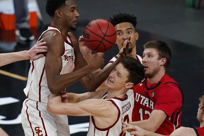 Southern California's Evan Mobley, from left, Drew Peterson and Utah's Eli Ballstaedt vie fore a rebound during the second overtime of an NCAA college basketball game in the quarterfinal round of the Pac-12 men's tournament Thursday, March 11, 2021, in Las Vegas. (AP Photo/John Locher)