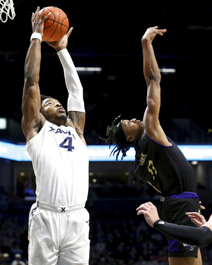 Xavier forward Tyrique Jones (4) catches a pass over Western Carolina forward Xavier Cork (13) during the first half of an NCAA college basketball game, Wednesday, Dec. 18, 2019 in Cincinnati. (Kareem Elgazzar/The Cincinnati Enquirer via AP)