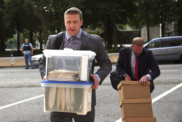 FILE - In this Aug. 1, 2017 file photo, former St. Louis city police officer Jason Stockley, 36, left, arrives with his legal team at the Carnahan Courthouse in St. Louis. A judge has dismissed the malicious prosecution and defamation lawsuit filed by the white former St. Louis police officer whose acquittal in the death of a black suspect set off weeks of protests. The St. Louis Post-Dispatch reports that U.S. District Judge Charles Shaw issued the 58-page ruling dropping Jason Stockley's lawsuit Thursday,. Feb. 14, 2019. (Laurie Skrivan/St. Louis Post-Dispatch via AP, File)
