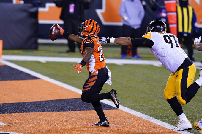 Cincinnati Bengals' Giovani Bernard (25) runs past Pittsburgh Steelers' Cameron Heyward (97) for a touchdown reception during the first half of an NFL football game, Monday, Dec. 21, 2020, in Cincinnati. (AP Photo/Michael Conroy)