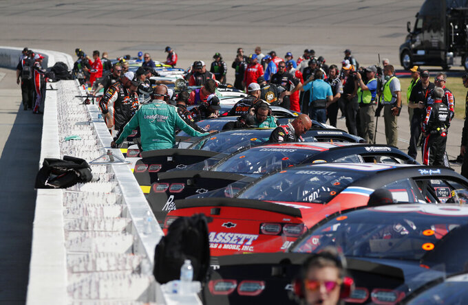 Drivers climb into their cars as crews get ready for a NASCAR Xfinity Series auto race, Saturday, July 27, 2019, at Iowa Speedway in Newton, Iowa. (AP Photo/Matthew Putney)