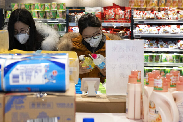 In this Tuesday, Feb. 18, 2020, photo, shoppers look at antiseptic gel on sale at the 7Fresh supermarket in Beijing. Stores that offer online purchases are enjoying brisk sales as residents avoid going out during the current viral outbreak with authorities last week requiring people returning to the capital to self-quarantine at home or in a concentrated area for medical observation.(AP Photo/Ng Han Guan)