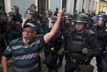 Police block demonstrators from advancing to La Fortaleza governor's residence in San Juan, Puerto Rico, Sunday, July 14, 2019. Protesters are demanding Gov. Ricardo Rosselló step down for his involvement in a private chat in which he used profanities to describe an ex-New York City councilwoman and a federal control board overseeing the island's finance. (AP Photo/Carlos Giusti)