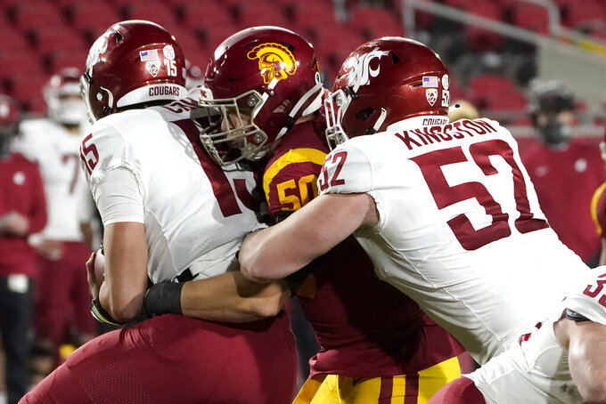 Southern California defensive lineman Nick Figueroa, center, brings down Washington State quarterback Gunner Cruz, left, with offensive lineman Jarrett Kingston during the second half of an NCAA college football game in Los Angeles, Sunday, Dec. 6, 2020. (AP Photo/Alex Gallardo)