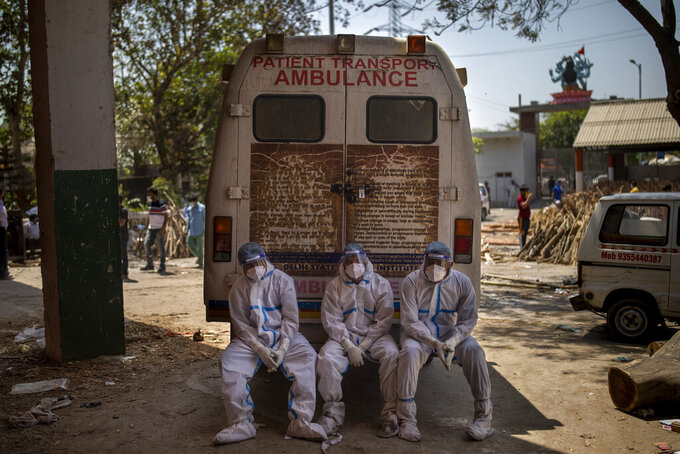 FILE - In this April 24, 2021, file photo, exhausted workers who carried the dead for cremation sit on the rear step of an ambulance in New Delhi, India. As deaths mount and a vaccine rollout falters badly, Prime Minister Narendra Modi has pushed much of the responsibility for fighting the outbreak onto unprepared and poorly equipped state governments. The crisis has badly dented Modi's carefully cultivated image as an able technocrat.  (AP Photo/Altaf Qadri, File)