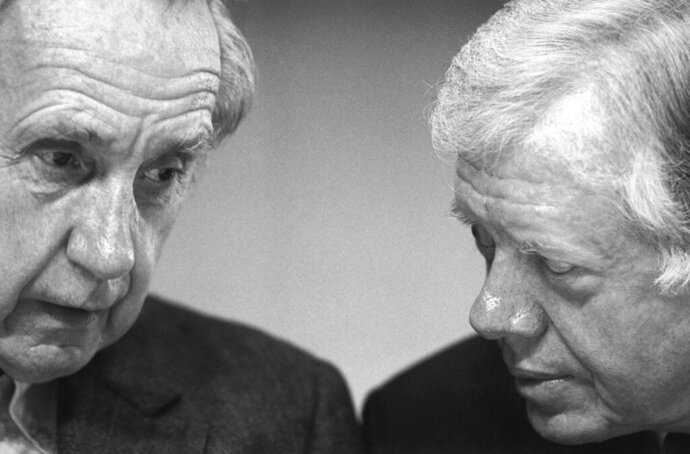 FILE - In this Nov. 17, 1987 file photo, Sir Brian Urquhart, former under secretary-general of the United Nations, left, and former President Jimmy Carter confer during the opening session of a Middle East conference held at the Carter Center in Atlanta, Ga. Urquhart, who played a central role in developing the U.N. practice of peacekeeping, died at his home in Tyringham, Mass., on Saturday, Jan. 2, 2021, according to his family, reported by the New York Times. He was 101. (AP Photo/Linda Schaefer)