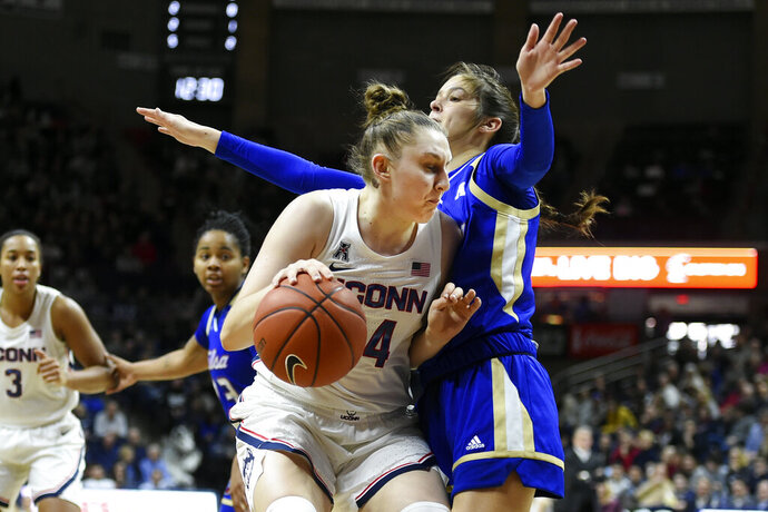 Connecticut's Anna Makurat (24) tries to get around Tulsa's Addison Richards (4) during the first half of an NCAA college basketball game Sunday, Jan. 19, 2020, in Storrs, Conn. (AP Photo/Stephen Dunn)
