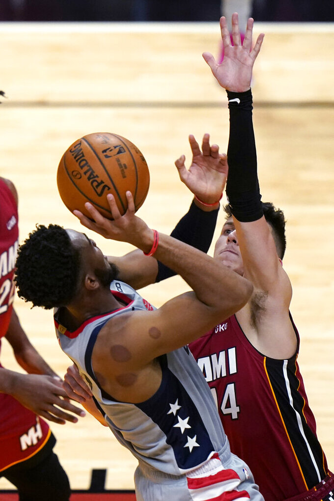 Miami Heat guard Tyler Herro (14) defends against Washington Wizards forward Troy Brown Jr. during the first half of an NBA basketball game Wednesday, Feb. 3, 2021, in Miami. (AP Photo/Lynne Sladky)