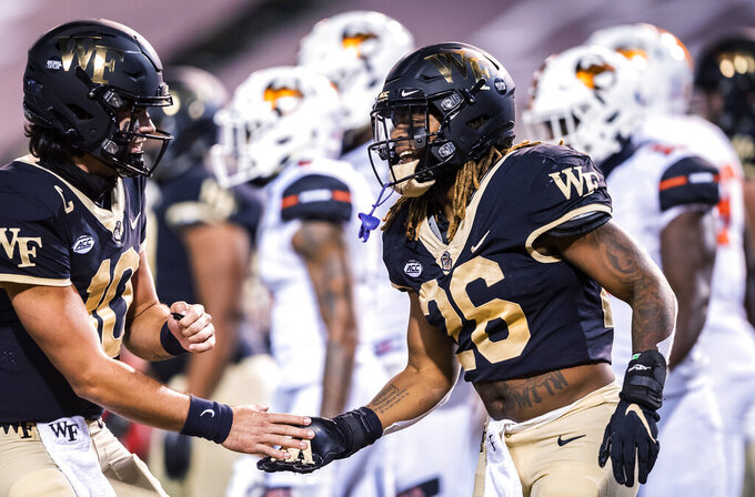 Wake Forest running back Christian Beal-Smith (26) celebrates his touchdown with quarterback Sam Hartman (10) during an NCAA college football game against Campbell on Friday, Oct. 2, 2020, in Winston-Salem, N.C. (Andrew Dye/The Winston-Salem Journal via AP)
