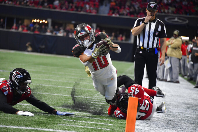 Tampa Bay Buccaneers wide receiver Scott Miller (10) stretches as Atlanta Falcons linebacker Deion Jones (45) defends during the first half of an NFL football game, Sunday, Nov. 24, 2019, in Atlanta. (AP Photo/John Amis)