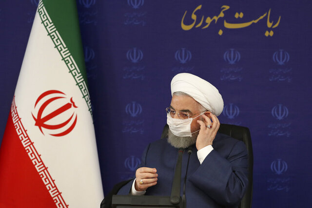 In this photo released by the official website of the office of the Iranian Presidency, President Hassan Rouhani adjusts his face mask in a meeting of the national headquarters of the fight against the COVID-19, in Tehran, Iran, Saturday, July 18, 2020. He estimated as many as 25 million Iranians could have been infected with the coronavirus since the outbreak's beginning, citing an Iranian Health Ministry study that has so far not been made public, the state-run IRNA news agency reported. Writing in Farsi at top right reads,