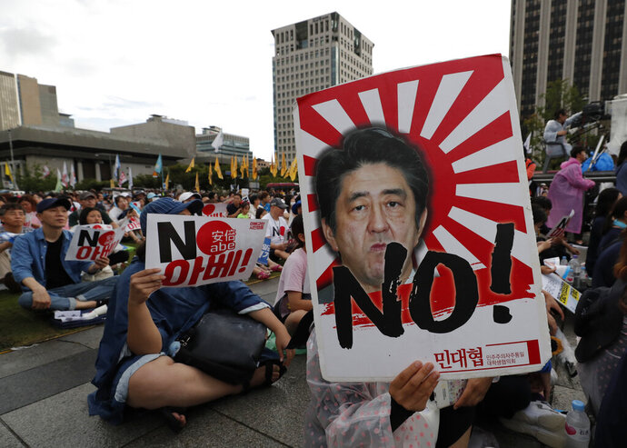 FILE - In this Aug. 15, 2019, file photo, a protester holds an image of Japanese Prime Minister Shinzo Abe during a rally denouncing Abe and also demanding the South Korean government to abolish the General Security of Military Information Agreement, or GSOMIA, an intelligence-sharing agreement between South Korea and Japan, in downtown Seoul, South Korea. Squeezed between a growing North Korean threat and a shaky alliance with the United States, South Korea must decide this week whether its national pride and deep frustrations with Japan are worth killing a major symbol of their security cooperation with Washington. The letters read