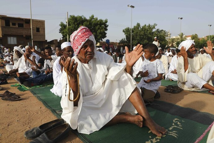 """FILE - In this May 24, 2020 file photo, Sudanese worshippers gather for Eid al-Fitr prayers, the Muslim holiday which starts at the conclusion of the holy fasting month of Ramadan, in Khartoum, Sudan. The International Monetary Fund has signed off on Sudan's economic reform program, a move that can eventually allow the highly-indebted African country receive debt reliefs and hence rebuild its battered economy. The IMF released a statement Wednesday, Sept. 23, 2020,  saying that its staff will be monitoring the implementation of a """"home-grown"""" economic restructuring program. (AP Photo/Marwan Ali, file)"""