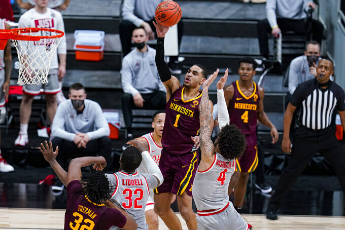 Minnesota guard Tre' Williams (1) shoots over Ohio State guard Duane Washington Jr. (4) in the first half of an NCAA college basketball game at the Big Ten Conference tournament in Indianapolis, Thursday, March 11, 2021. (AP Photo/Michael Conroy)
