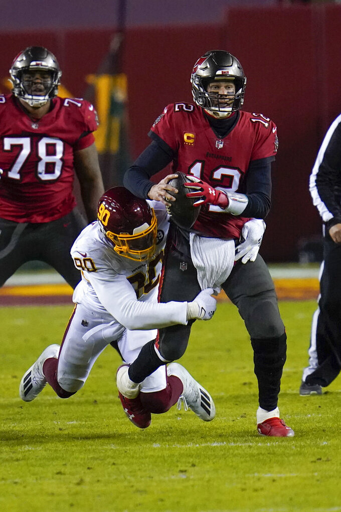 Tampa Bay Buccaneers quarterback Tom Brady (12) is sacked by Washington Football Team defensive end Montez Sweat (90) during the first half of an NFL wild-card playoff football game, Saturday, Jan. 9, 2021, in Landover, Md. (AP Photo/Julio Cortez)