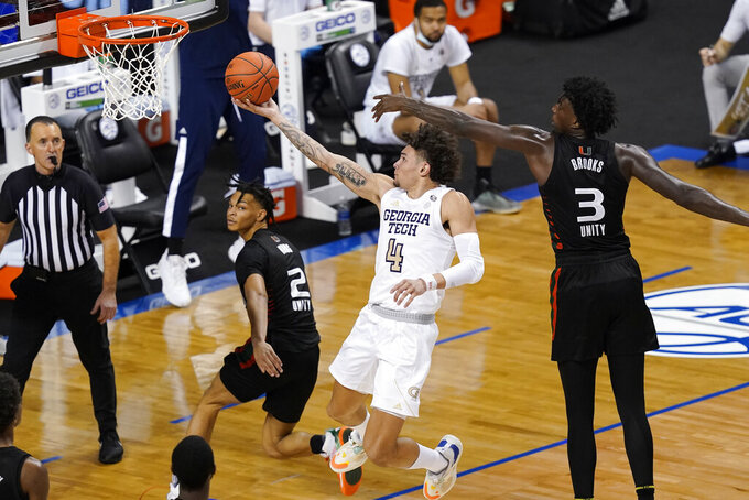 Georgia Tech guard Jordan Usher (4) goes up for a shot as Miami guard Isaiah Wong (2) and teammate center Nysier Brooks (3) defend during the second half of an NCAA college basketball game in the quarterfinal round of the Atlantic Coast Conference tournament in Greensboro, N.C., Thursday, March 11, 2021. (AP Photo/Gerry Broome)