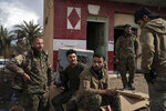 U.S.-backed Syrian Democratic Forces (SDF) fighters stand outside a building used as a temporary base near the last land still held by Islamic State militants in Baghouz, Syria, Monday, Feb. 18, 2019. Hundreds of Islamic State militants are surrounded in a tiny area in eastern Syria are refusing to surrender and are trying to negotiate an exit, Syrian activists and a person close to the negotiations said Monday. (AP Photo/Felipe Dana)