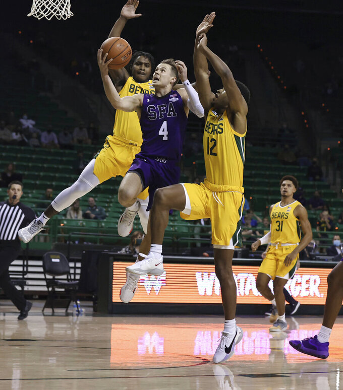Stephen F. Austin guard David Kachelries, center, shoots between Baylor guards Davion Mitchell, left, and Jared Butler, right, during the first half of an NCAA college basketball game Wednesday, Dec. 9, 2020, in Waco, Texas. (Rod Aydelotte/Waco Tribune Herald via AP)