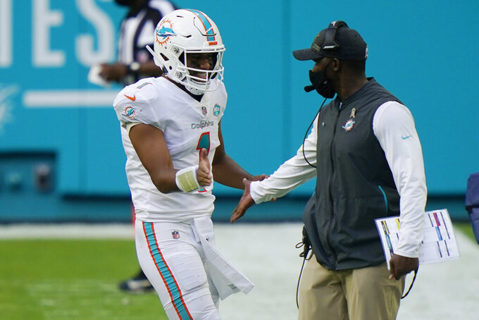 Miami Dolphins head coach Brian Flores congratulates quarterback Tua Tagovailoa (1) after a touchdown, during the first half of an NFL football game against the Los Angeles Rams, Sunday, Nov. 1, 2020, in Miami Gardens, Fla. (AP Photo/Lynne Sladky)