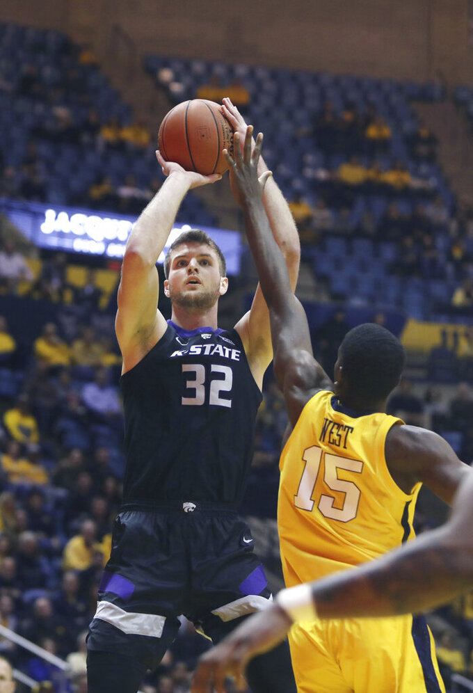 Kansas State forward Dean Wade (32) shoots while defended by West Virginia forward Lamont West (15) during the first half/second half of an NCAA college basketball game Monday, Feb. 18, 2019, in Morgantown, W.Va. (AP Photo/Raymond Thompson)