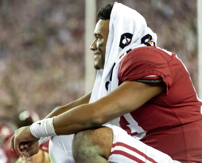 Alabama quarterback Tua Tagovailoa (13) smiles as he watches second stringers finish an NCAA college football game against Auburn during the second half Saturday, Nov. 24, 2018, in Tuscaloosa, Ala. (AP Photo/Vasha Hunt)