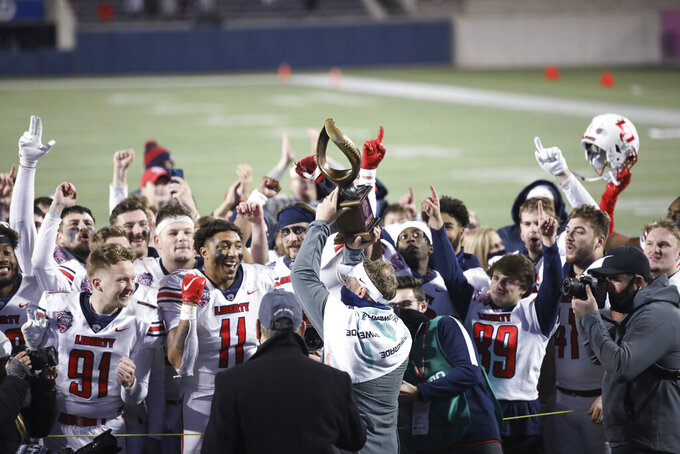 Liberty coach Hugh Freeze holds the trophy and celebrates with players after the team's overtime win over Coastal Carolina in the Cure Bowl NCAA college football game Saturday, Dec. 26, 2020, in Orlando, Fla. (AP Photo/Matt Stamey)