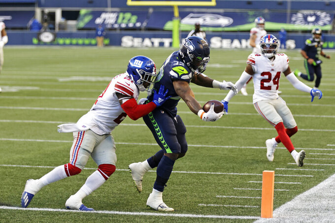 Seattle Seahawks running back Chris Carson, center scores a touchdown after a reception ahead of New York Giants safety Jabrill Peppers (21) during the second half of an NFL football game, Sunday, Dec. 6, 2020, in Seattle. (AP Photo/Larry Maurer)