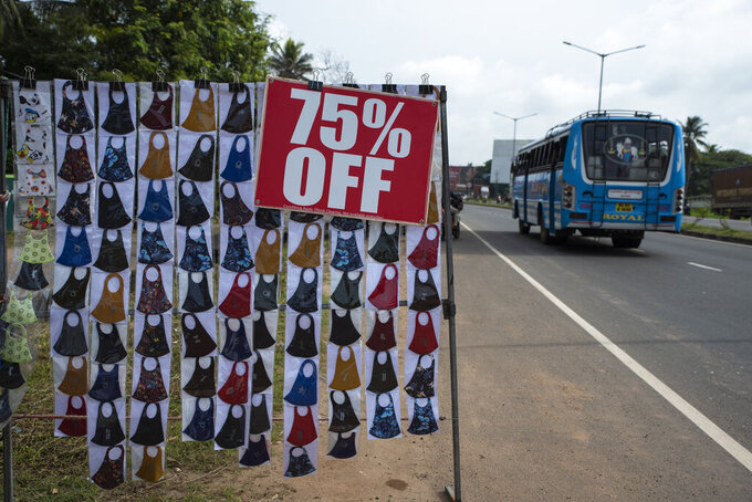 Face masks are displayed for sale by the side of a highway in Kochi, Kerala state, India, Monday, Sept.20, 2021. The tiny southern state continues to battle the highest number of coronavirus cases in the country. (AP Photo/R S Iyer)