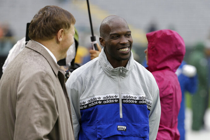 "FILE - In this Sept. 22, 2019, file photo, former NFL football player player Chad Johnson, right, talks with Green Bay Packers president and chief executive officer Mark Murphy before the start of a game between the Denver Broncos and Green Bay Packers in Green Bay, Wis. Chad Johnson left a whooping $1,000 tip for his waiter after dining at a restaurant in Florida that recently reopened amid the coronavirus outbreak. ""Congrats on re-opening, sorry about the pandemic, hope this helps. I LOVE YOU,"" Johnson wrote Monday, May 18, 2020, on his $37 tab. (AP Photo/Mike Roemer, File)"