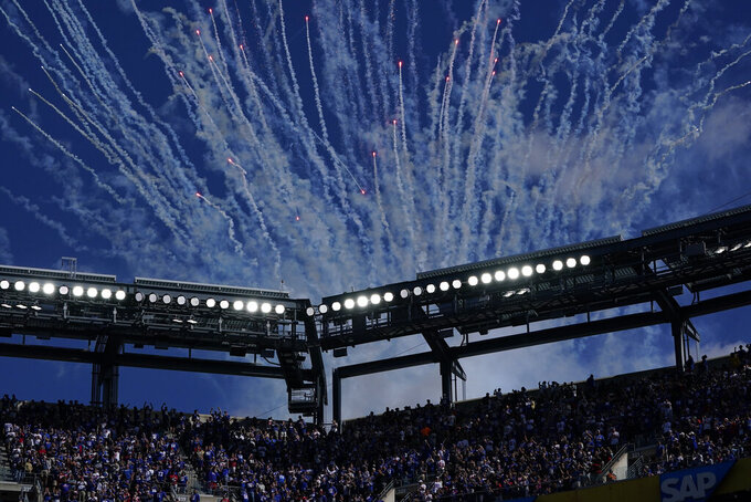 Fireworks are launched to honor former New York Giants quarterback Eli Manning as he addresses the crowd during a ceremony to retire his jersey number 10 and celebrate his tenure with the team during half-time in an NFL football game against the Atlanta Falcons, Sunday, Sept. 26, 2021, in East Rutherford, N.J. (AP Photo/Seth Wenig)