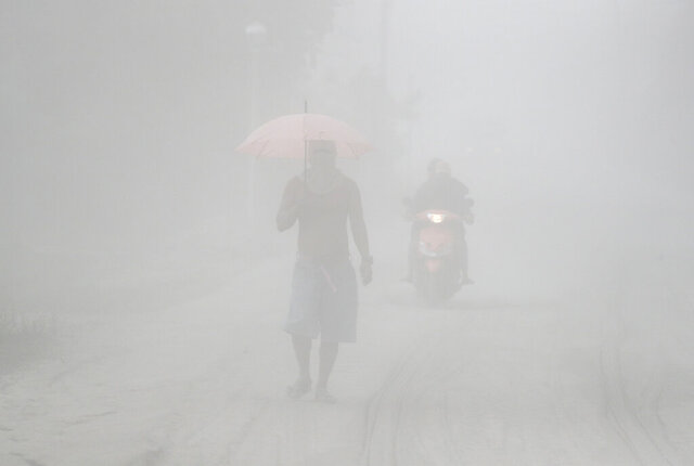 In this Monday, Jan. 13, 2020, photo, a man walks through a cloud of volcanic ash as he evacuates to safer grounds as Taal volcano in Lemery, Batangas province, southern Philippines. Red-hot lava is gushing from the volcano after a sudden eruption of ash and steam that forced residents to flee and shut down Manila's airport, offices and schools. (AP Photo/Aaron Favila)