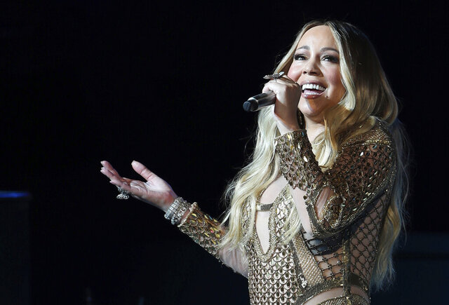 """FILE - In this Oct. 20, 2019 file photo Mariah Carey performs during a concert celebrating Dubai Expo 2020 One Year to Go in Dubai, United Arab Emirates. Christmas has come early for Carey: the pop star's original holiday classic, """"All I Want for Christmas Is You,"""" has reached the No. 1 spot on the Billboard Hot 100 chart 25 years after its release. Billboard announced that the song topped this week's chart, giving Carey her 19th No. 1 of her career.  (AP Photo/Kamran Jebreili, File)"""