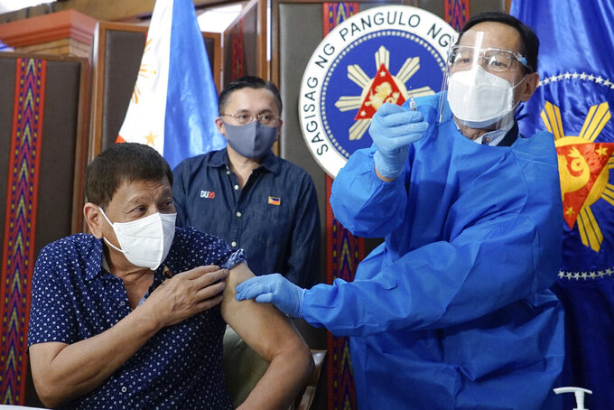 In this photo released by the Malacanang Presidential Photographers Division, President Rodrigo Duterte, left, prepares for his second dose of the COVID-19 Sinopharm vaccine by Health Secretary Francisco Duque III, right, in Malacañang Presidential palace, Manila on Monday, July 12, 2021. (King Rodriguez/Malacanang Presidential Photographers Division via AP)