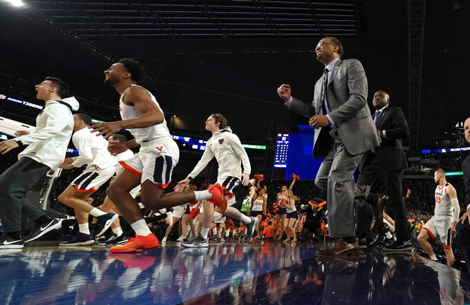 Virginia players and coaches celebrate at the end of a semifinal round game against Auburn in the Final Four NCAA college basketball tournament, Saturday, April 6, 2019, in Minneapolis. (AP Photo/David J. Phillip)