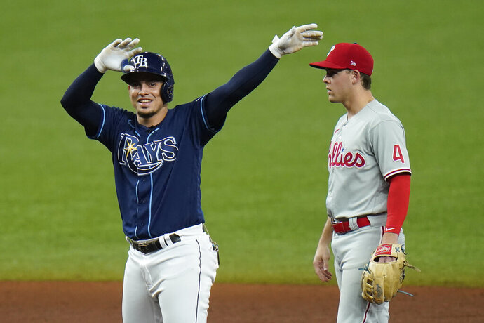 Tampa Bay Rays' Willy Adames celebrates after hitting an RBI double off Philadelphia Phillies starting pitcher Zack Wheeler during the fifth inning of a baseball game Saturday, Sept. 26, 2020, in St. Petersburg, Fla. Looking on is Phillies' Scott Kingery (4). (AP Photo/Chris O'Meara)