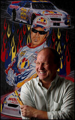 "FILE - In this July 24, 2006, file photo, artist Sam Bass, stands next to a poster he created for the movie, ""Talladega Nights: The Ballad of Ricky Bobby,"" starring Will Ferrell at his Concord, N.C. studio. Bass, NASCAR's first officially licensed artist, has died following a battle with kidney problems. He was 57.    (Jeff Siner/The Charlotte Observer via AP, File)"