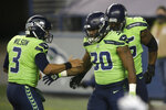 Seattle Seahawks quarterback Russell Wilson (3) greets running back Carlos Hyde (30) after Hyde scored a touchdown against the Arizona Cardinals during the second half of an NFL football game, Thursday, Nov. 19, 2020, in Seattle. (AP Photo/Lindsey Wasson)
