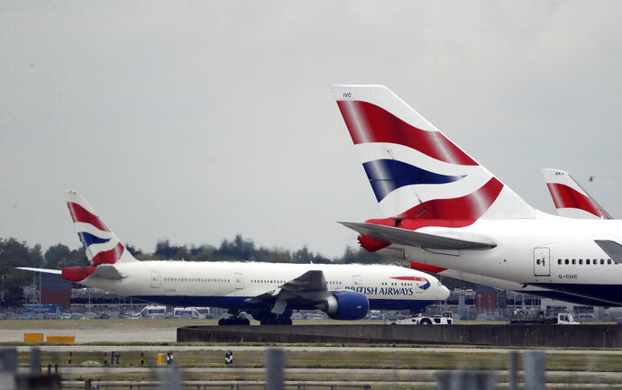 FILE - In this Monday, Sept. 9, 2019 file photo, a British Airways plane, at left, is towed past other planes sitting parked at Heathrow Airport in London. British Airways and Asian budget carriers Lion Air and Seoul Air are suspending all flights to China as fears spread about the outbreak of a new virus that has killed more than 130 people. British Airways said Wednesday, Jan. 29, 2020, it is immediately suspending all flights to and from mainland China after the U.K. government warned against unnecessary travel to the country. (AP Photo/Matt Dunham, File)