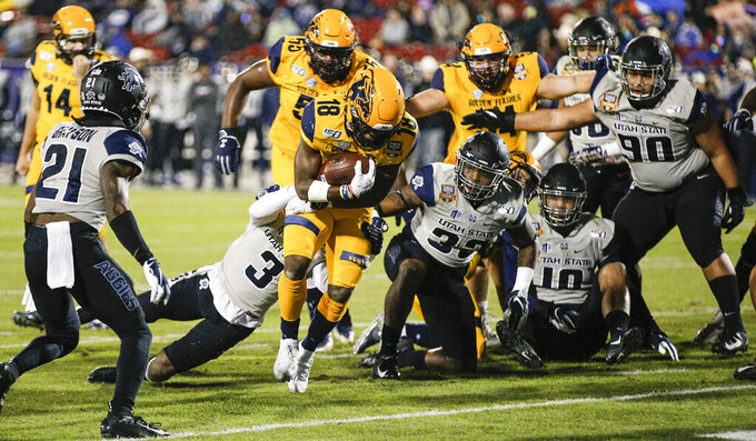 Kent State running back Xavier Williams (18) scores a touchdown as Utah State safety Troy Lefeged Jr. (3) defends during the first half of the Frisco Bowl NCAA college football game Friday, Dec. 20, 2019, in Frisco, Texas. (AP Photo/Brandon Wade)