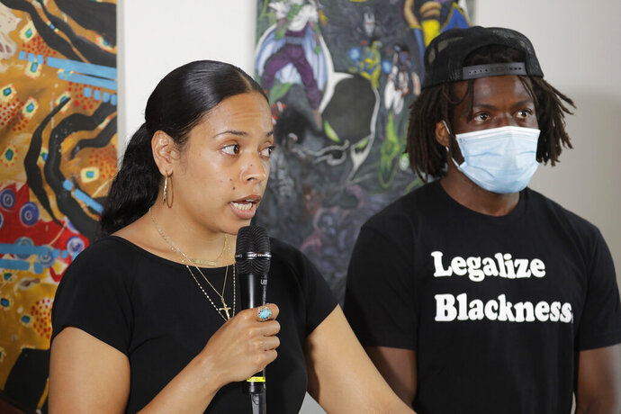 Naudia Miller, left, and Marcus Henderson, right, both of Black Collective Voices, speak Thursday, June 25, 2020, at a news conference in Seattle. Miller said the goal of protesters who have been active in the CHOP (Capitol Hill Occupied Protest) zone and elsewhere in the city since the death of George Floyd in Minneapolis is to dismantle systemic racism and to continue organizing until all of their demands are met. (AP Photo/Ted S. Warren)