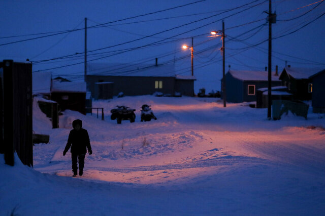 FILE - In this Jan. 20, 2020, file photo, a woman walks before dawn in Toksook Bay, Alaska, a mostly Yuip'ik village on the edge of the Bering Sea. Native American leaders are raising questions about how $8 billion in federal coronavirus relief tagged for tribes will be distributed, with some arguing that for-profit Alaska Native corporations shouldn't get a share of the funding. (AP Photo/Gregory Bull, File)