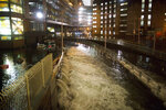 FILE - In this Oct. 29, 2012 file photo, seawater floods the entrance to the Brooklyn Battery Tunnel during Superstorm Sandy in New York. Mayor Bill de Blasio is announcing a plan, Thursday, March 14, 2019, to protect lower Manhattan from rising sea levels by surrounding it with earthen berms and extending its shoreline by as much as 500 feet. Officials have been developing schemes to fortify New York City's waterfront ever since Superstorm Sandy destroyed thousands of homes and businesses in 2012. (AP Photo/ John Minchillo, File)